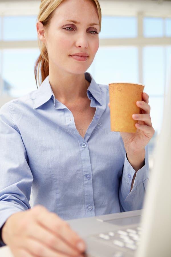 Affärskvinna med bärbar dator och kaffe royaltyfri bild