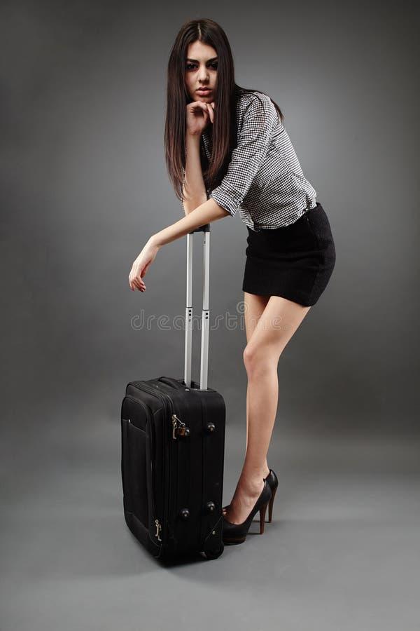 Affärskvinna med bagage över grå bakgrund royaltyfri foto