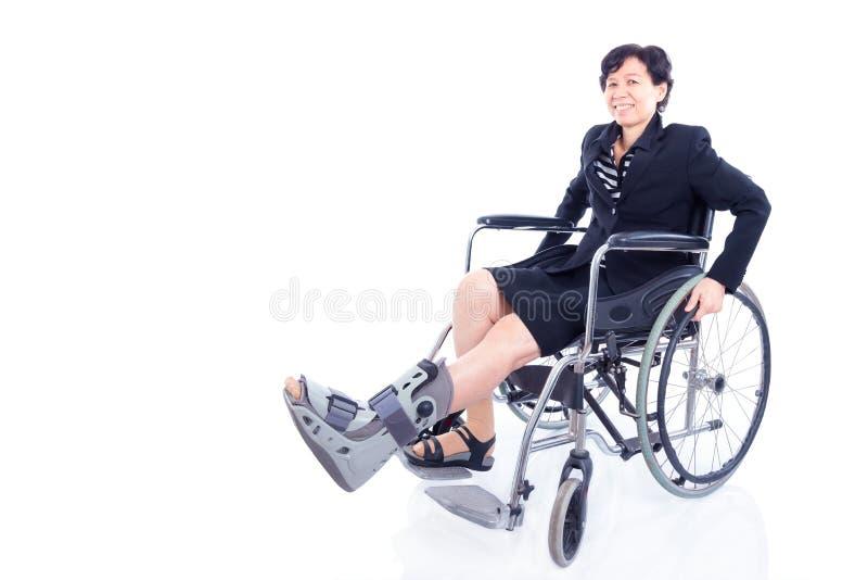 Affärskvinna med benstaget som sitter på rullstolen royaltyfria bilder