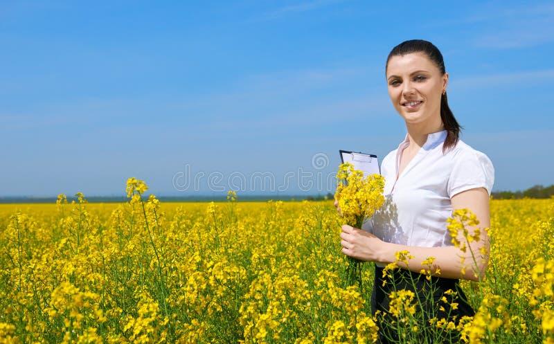 Affärskvinna med buketten och skrivplatta som kopplar av i det utomhus- blommafältet Ung flicka i gult rapsfröfält härligt vatten arkivfoton