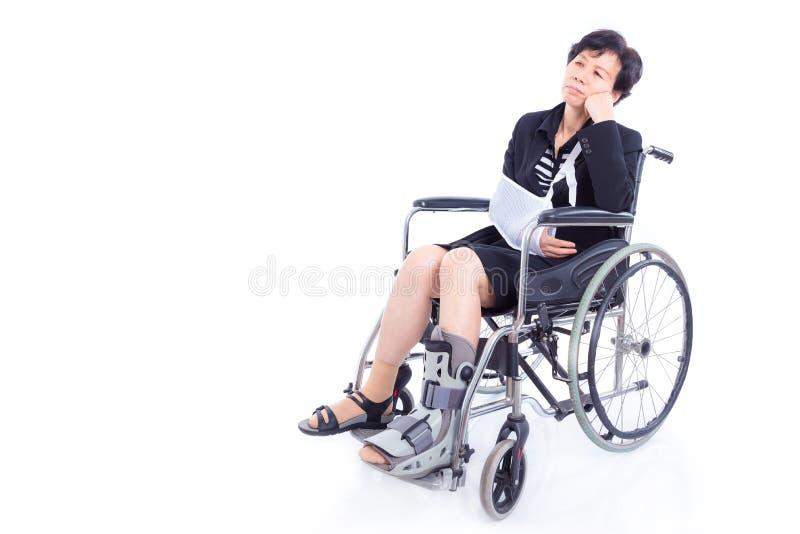 Affärskvinna med den brutna armen och benet som sitter på hjulstol arkivbild