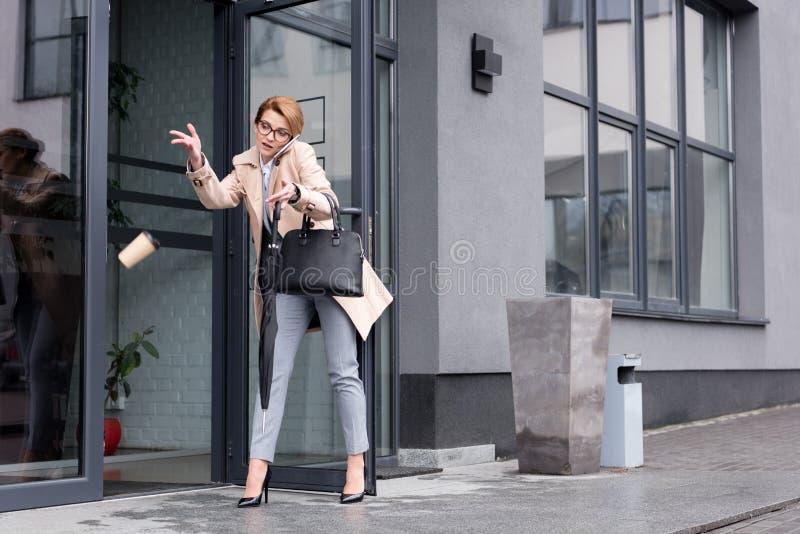 affärskvinna med den fallande disponibla koppen kaffe som talar på smartphonen, medan skriva in arkivfoton