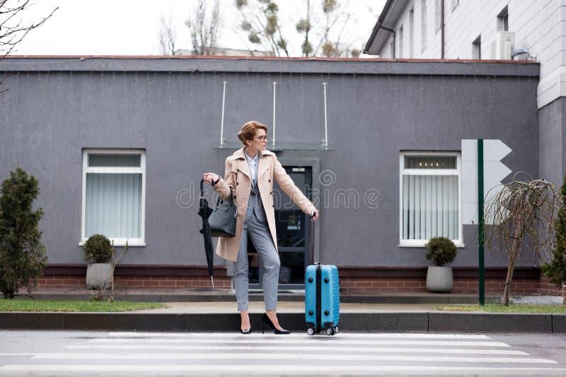 affärskvinna med den väntande på taxien för resväska och för paraply royaltyfri foto
