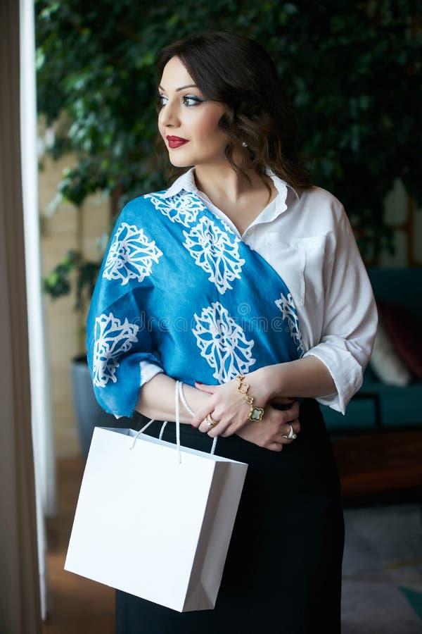Affärskvinna med den vita shoppa påsen som inomhus poserar royaltyfri bild
