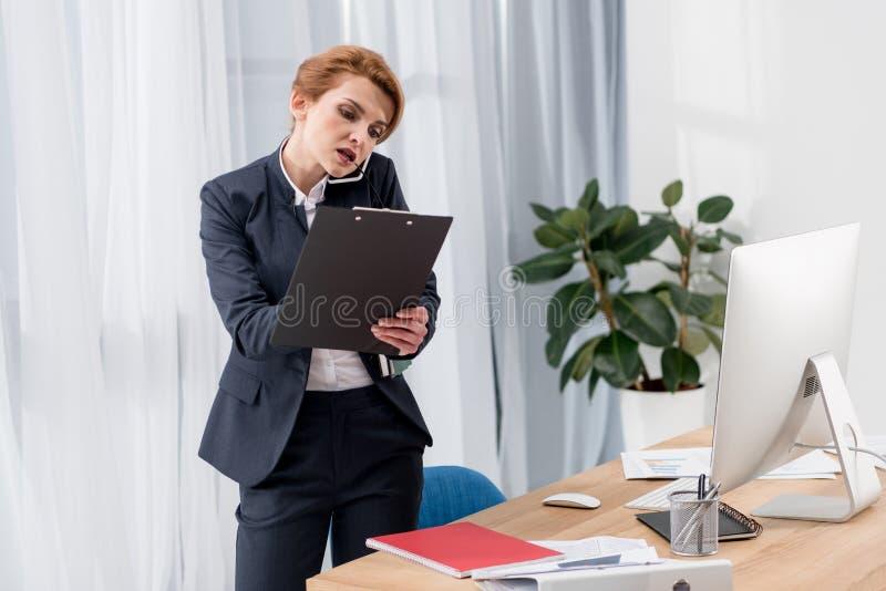 affärskvinna med dokument som talar på smartphonen på arbetsplatsen arkivbilder