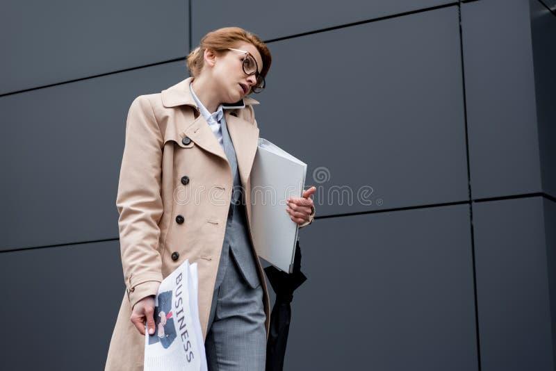 affärskvinna med dokument som talar på smartphonen arkivbilder