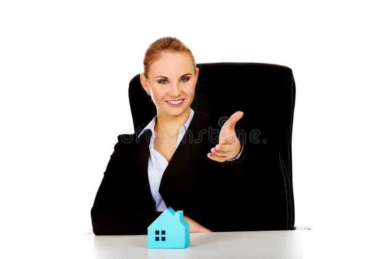 Affärskvinna med en öppen hand som är klar för hus för handskakning och för blått papper på skrivbordet fotografering för bildbyråer