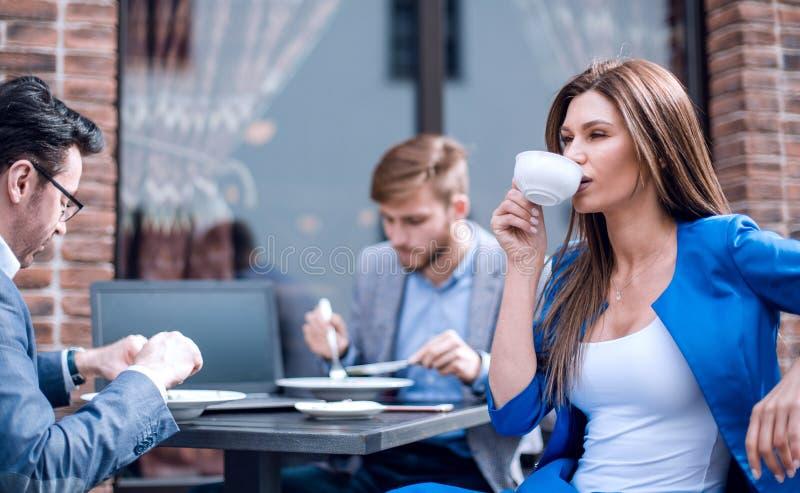 Affärskvinna med en kopp kaffe som sitter på en tabell i ett hemtrevligt kafé royaltyfri foto