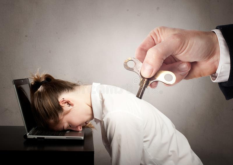 Affärskvinna med en nyckel- winder på henne tillbaka arkivfoto