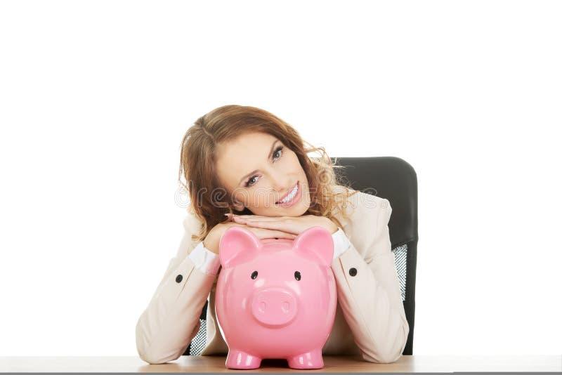 Affärskvinna med en piggybank royaltyfria bilder