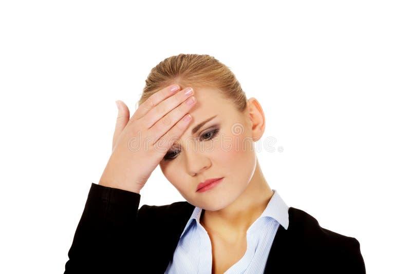 Affärskvinna med ett hållande huvud för enorm huvudvärk royaltyfri fotografi