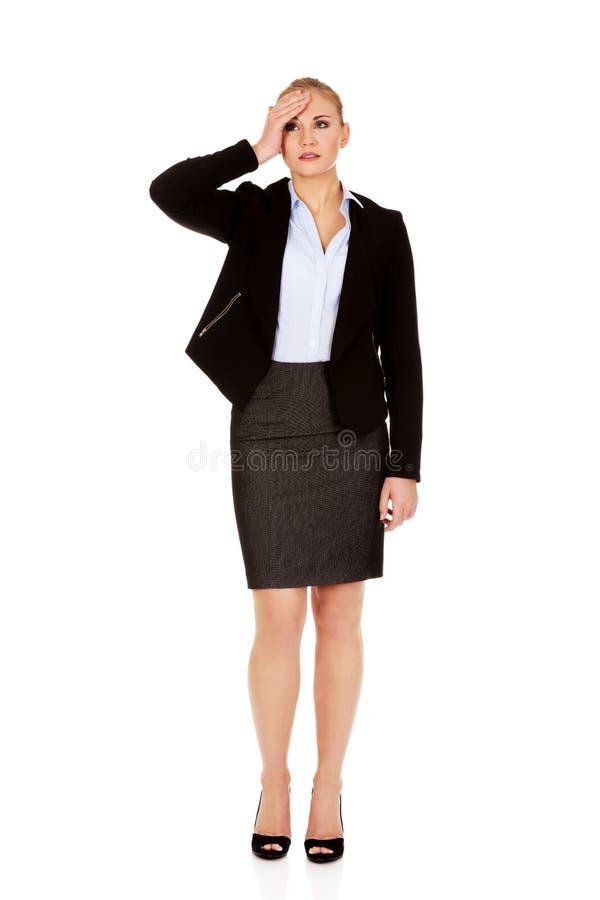 Affärskvinna med ett hållande huvud för enorm huvudvärk royaltyfri bild