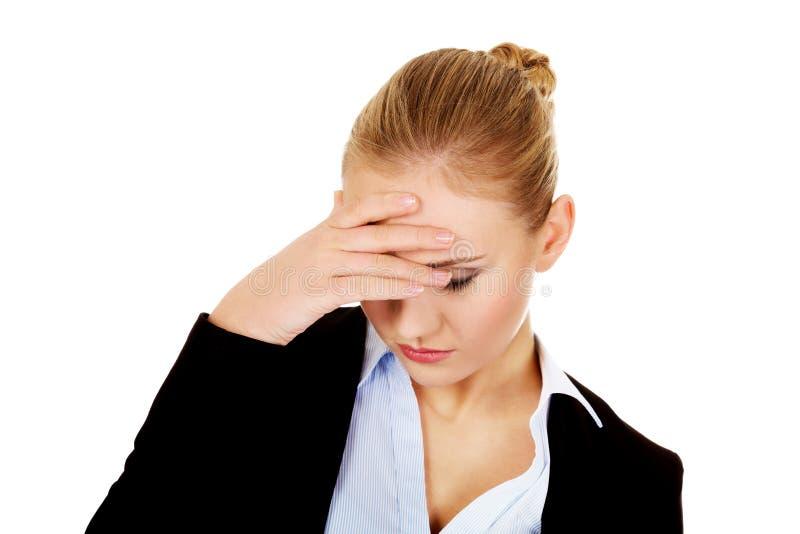 Affärskvinna med ett hållande huvud för enorm huvudvärk arkivfoto