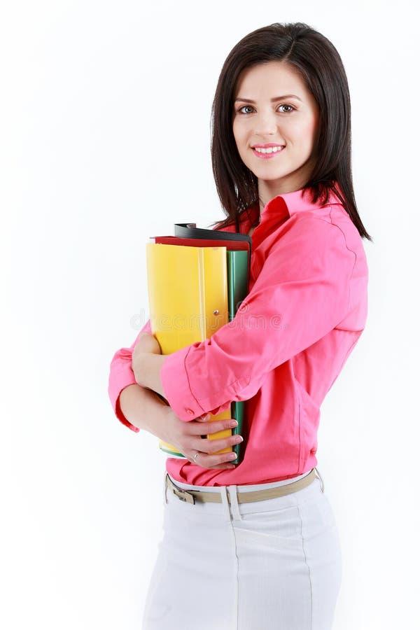 Affärskvinna med färgrika mappar som isoleras på vit backgroun arkivfoto