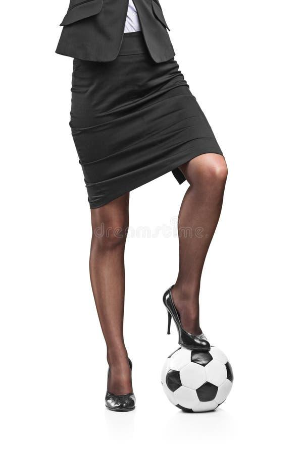 Affärskvinna med fotboll under hennes fot royaltyfria foton