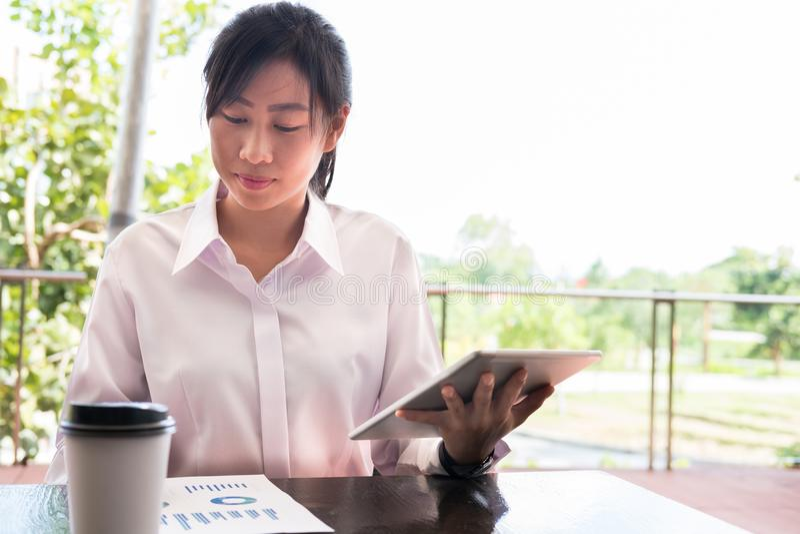Affärskvinna med grafsitt för digital minnestavla & för finansiell översikt royaltyfri fotografi