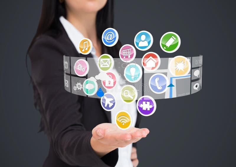 Affärskvinna med handspridning av och applikationsymboler som kommer upp från den Grå färgbakgrund royaltyfria foton