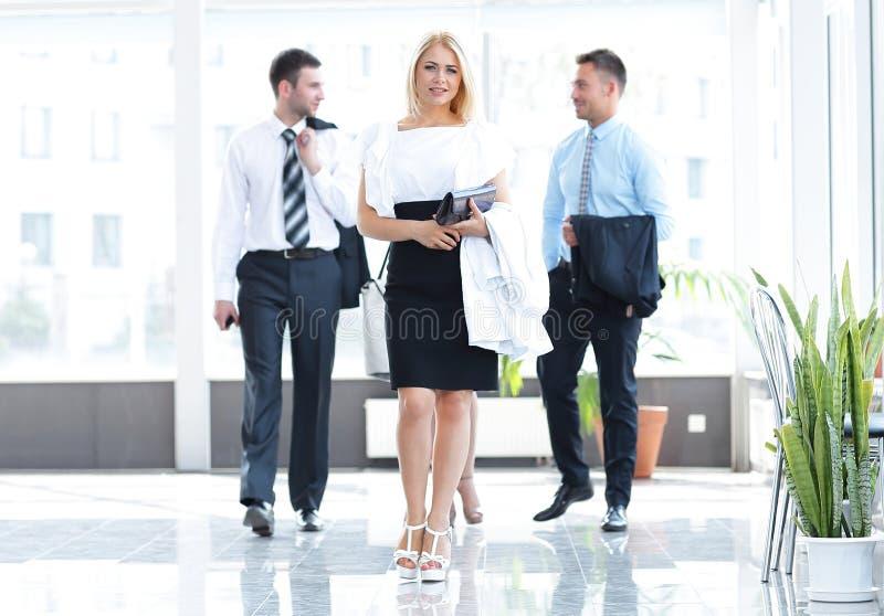 Affärskvinna med hennes kollegor som står i lobbyen av kontoret arkivfoto