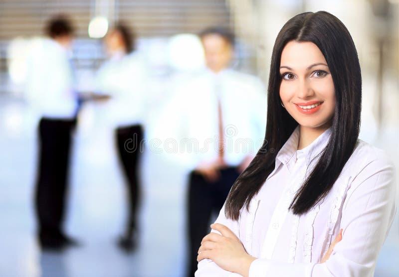 Affärskvinna med hennes personal, folkgrupp i bakgrund royaltyfria foton