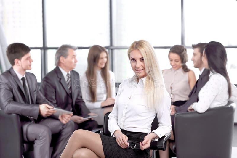 Affärskvinna med hennes personal, folkgrupp i bakgrund på det moderna ljusa kontoret royaltyfri fotografi