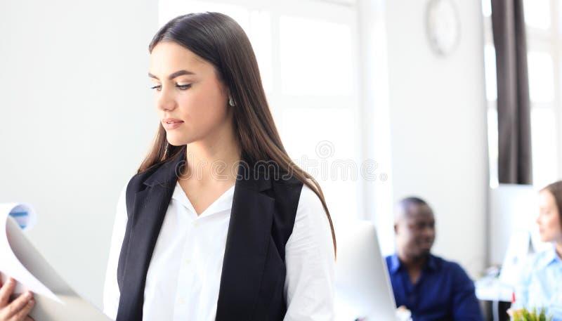 Affärskvinna med hennes personal, folkgrupp i bakgrund på det moderna ljusa kontoret arkivbild