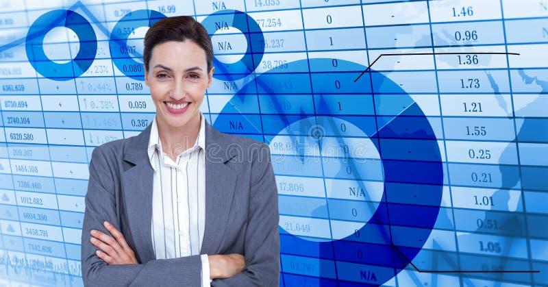 Affärskvinna med korsade armar framme av en blå tabell arkivfoton
