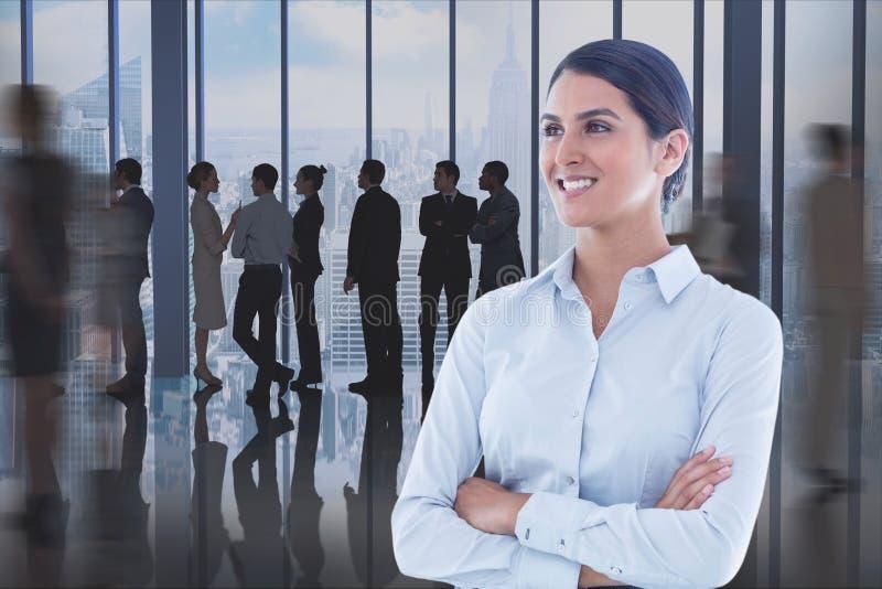 Affärskvinna med korsade armar mot kontorsbakgrund arkivfoto