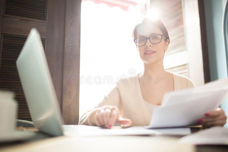 Affärskvinna med legitimationshandlingar och bärbara datorn som ser kameran royaltyfria foton