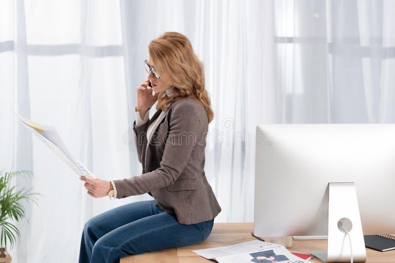 affärskvinna med legitimationshandlingar som talar på smartphonen, medan sitta på tabellen royaltyfri foto