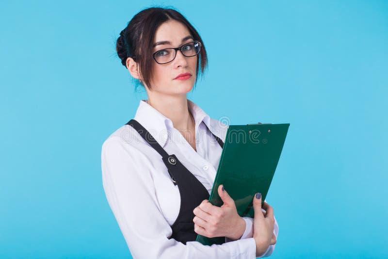 Affärskvinna med mappen på blå bakgrund arkivfoton