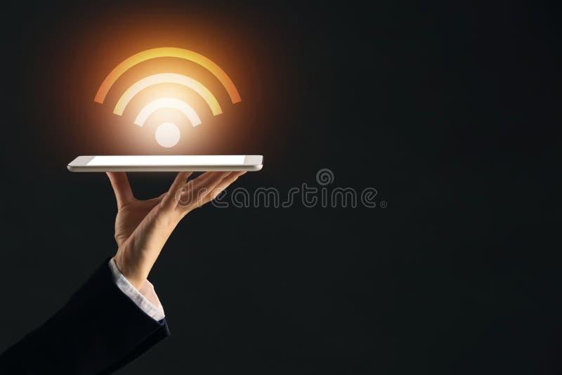 Affärskvinna med minnestavlaPC och symbol Wi-Fi på mörk bakgrund royaltyfri fotografi
