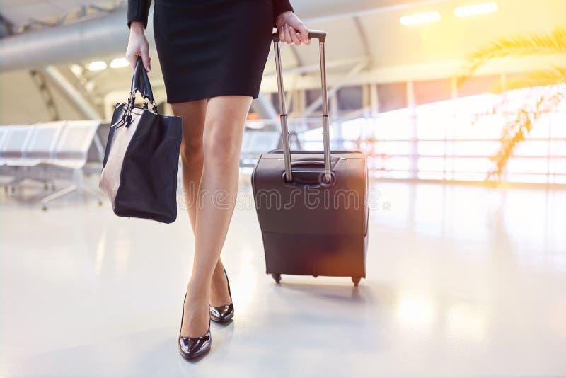 Affärskvinna med spårvagnresväskan på flygplatsen fotografering för bildbyråer