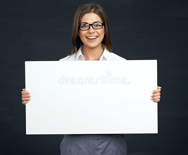 Affärskvinna med tomt brädeanseende mot svart bakgrund arkivbilder