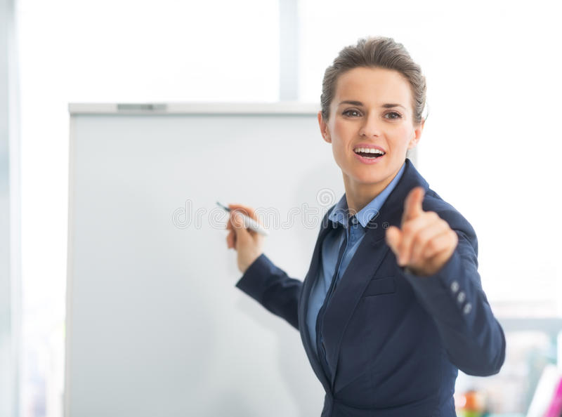 Affärskvinna nära flipchart som pekar på lyssnare arkivbild