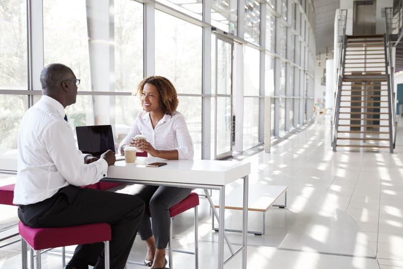 Affärskvinna och affärsman på ett möte som talar royaltyfri bild