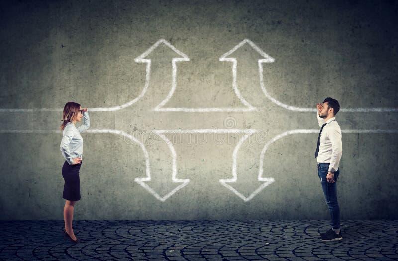 Affärskvinna och affärsman som ser in i framtiden som en tvärgatapilsplittring i tre andra sätt som finner en gemensam väg royaltyfria bilder