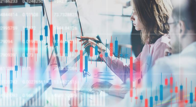 Affärskvinna och hennes kollega som sitter den främre bärbar datordatoren med finansiell grafer och statistik på bildskärm double arkivfoton