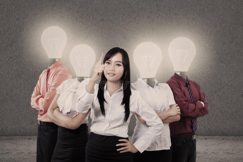 Affärskvinna och lag med huvud för ljus kula royaltyfri fotografi
