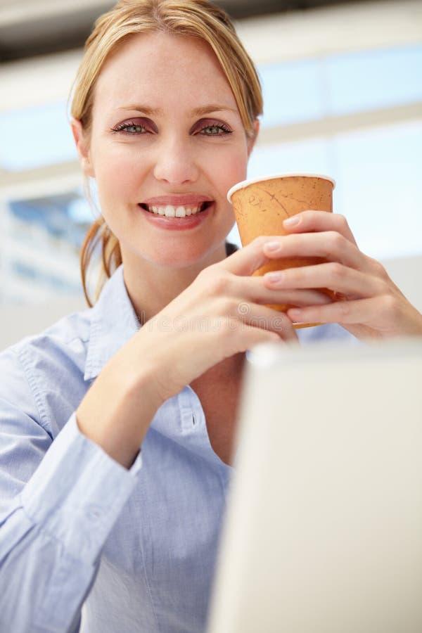 Affärskvinna på bärbar dator och kaffe arkivfoto
