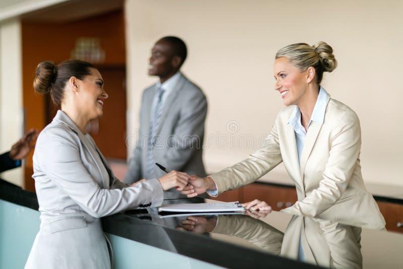Affärskvinna på hotellmottagandet royaltyfri foto