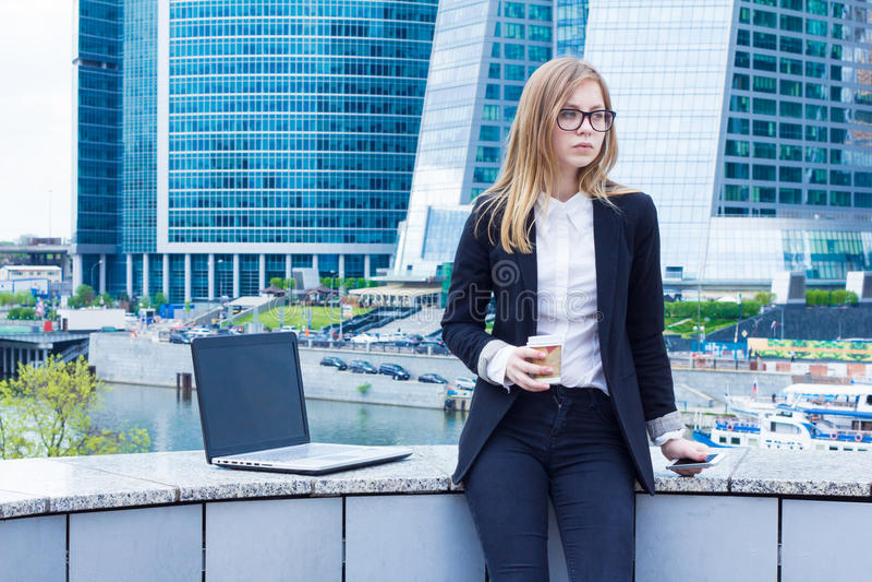 Affärskvinna på kaffeavbrott med ett bärbar datorsammanträde på gatan royaltyfria bilder