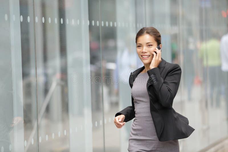 Affärskvinna på mobiltelefonrunning arkivbilder
