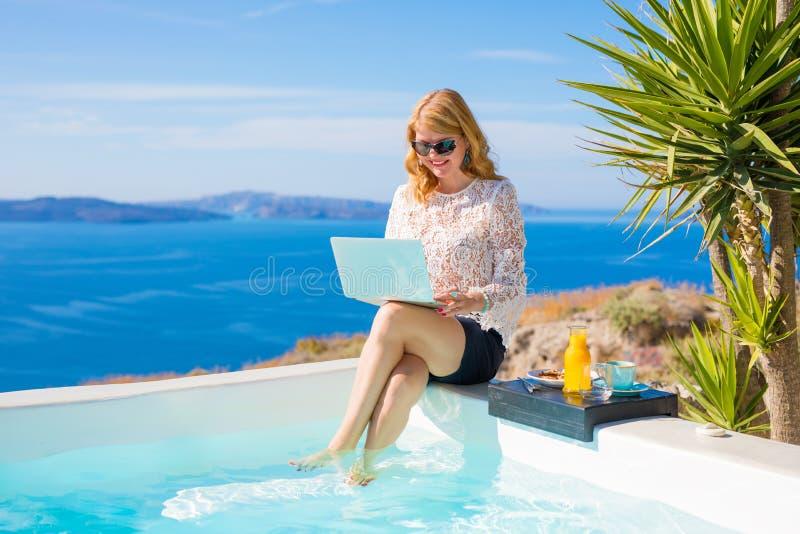 Affärskvinna på semestern som arbetar på bärbara datorn arkivfoton