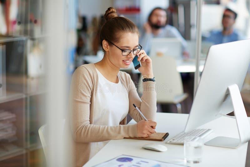 Affärskvinna på telefonen med partners arkivfoto