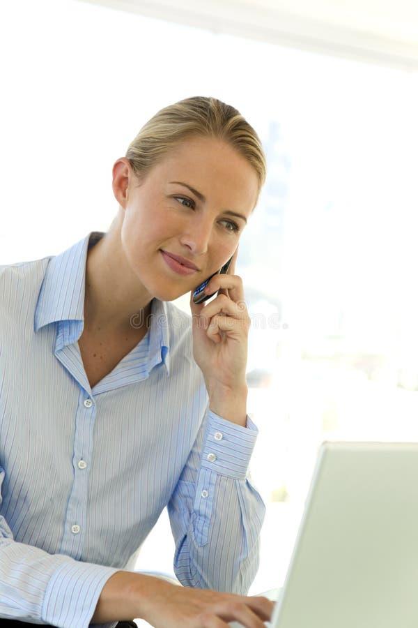 Affärskvinna på telefonen på arbetsplatsen royaltyfria bilder