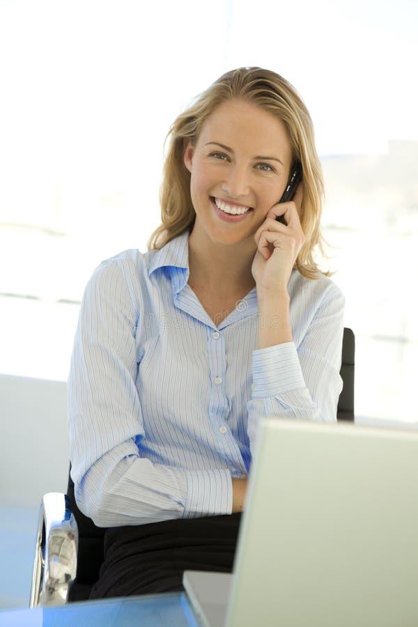 Affärskvinna på telefonen på arbetsplatsen royaltyfri bild