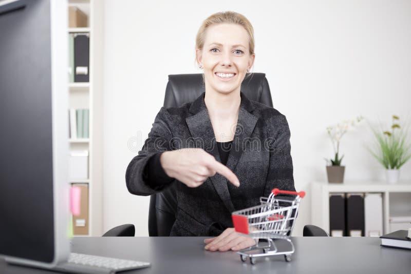 Affärskvinna Pointing på den lilla vagnen på hennes skrivbord arkivbilder