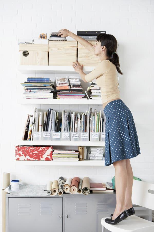 Affärskvinna Reaching For Shelf i inrikesdepartementet royaltyfri foto