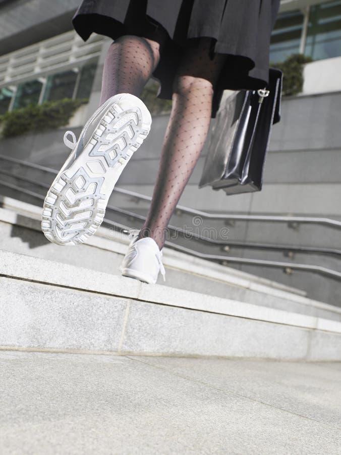 Affärskvinna In Running Shoes som går upp moment royaltyfri foto