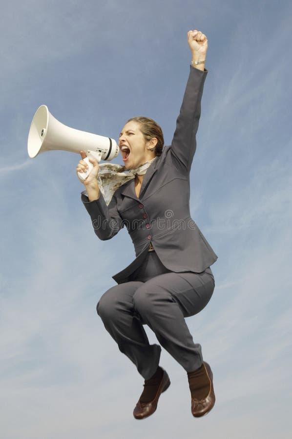 Affärskvinna Shouting Into Megaphone mot molnig himmel royaltyfri foto
